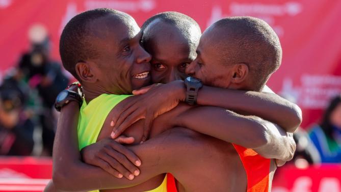 Ba vận động viên chiến thắng ở sự kiệnChicago Marathon (12/10/2014) ôm chầm lấy nhau sau khi về đích. Bên trái:Eliud Kipchoge (về nhất), ở giữa:Kenyans Sammy Kitwara (về nhì) và bên phải là Dickson Chumba (về ba)(AP Photo/Andrew A. Nelles)